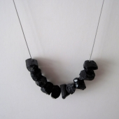 Graphic cluster of black rugged tourmaline nuggets hang on a minimalist steel st